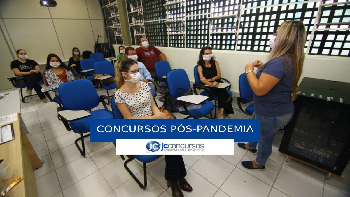Concursos pós-pandemia: com máscaras, pessoas ocupam ambiente fechado respeitando a distância apropriada em tempos de Covid-19